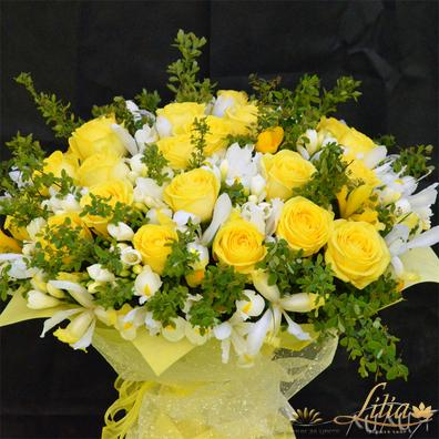A huge bouquet of yellow roses and freesia